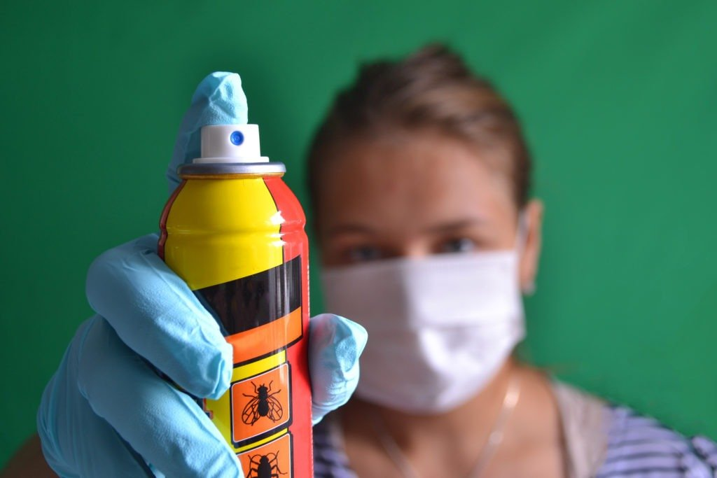 Woman with mask holding insect spray.